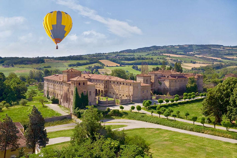 A hot air balloon flying over the Castelli del Ducato